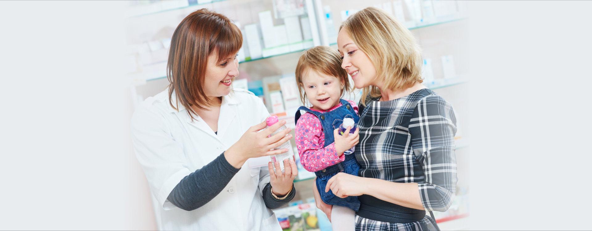 pharmacist chemist woman demonstrating cream gel to child girl